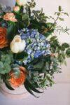 Ramo de flores con hortensias, presentado en una caja redonda de terciopelo con letras doradas.